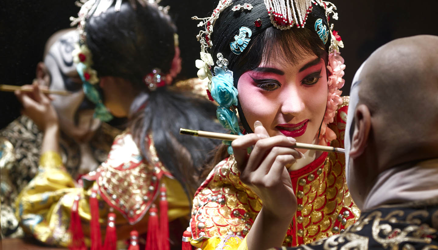 China (Volksrepublik) - Chinese opera singer applying makeup to male