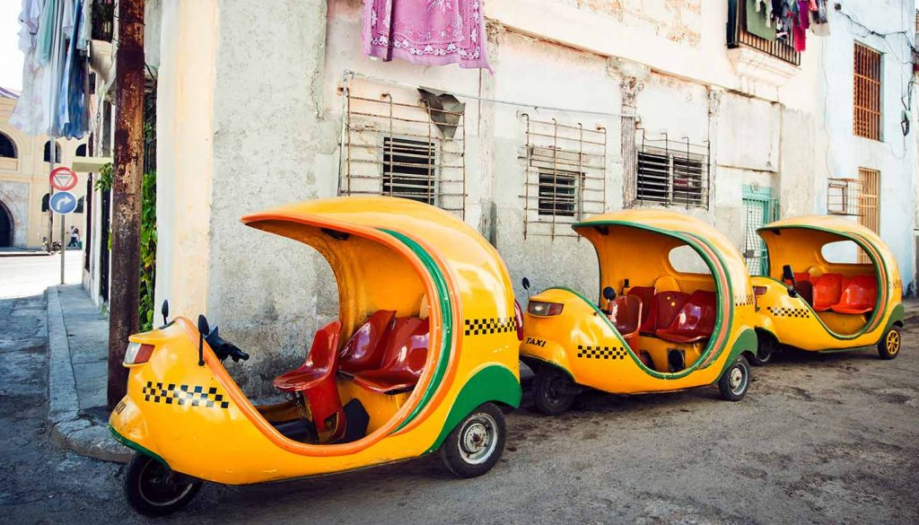 Kuba - Coco-taxis parked at a street of Havana