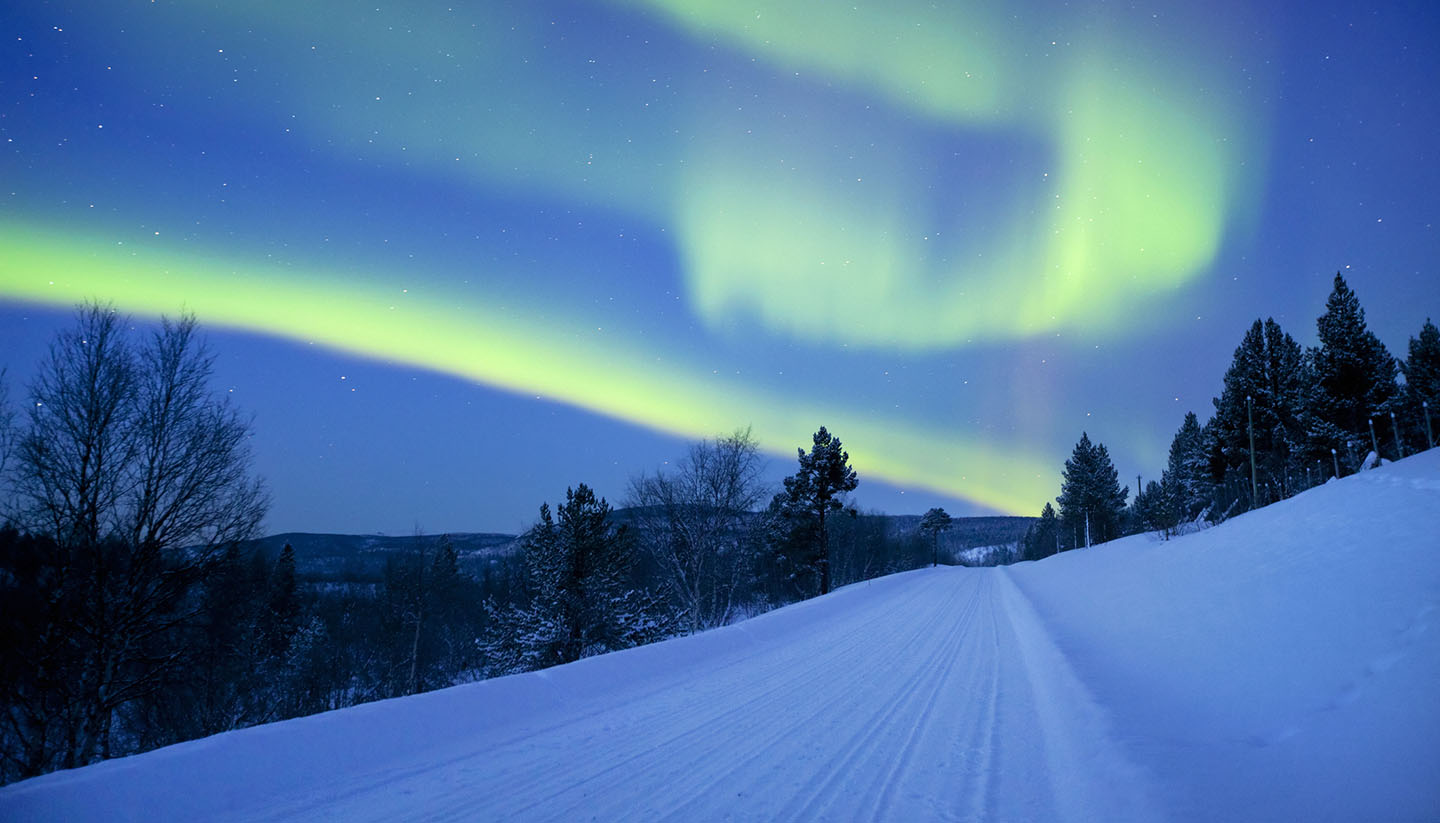 Finnland - Aurora borealis over a road through winter landscape, Finnish Lapland