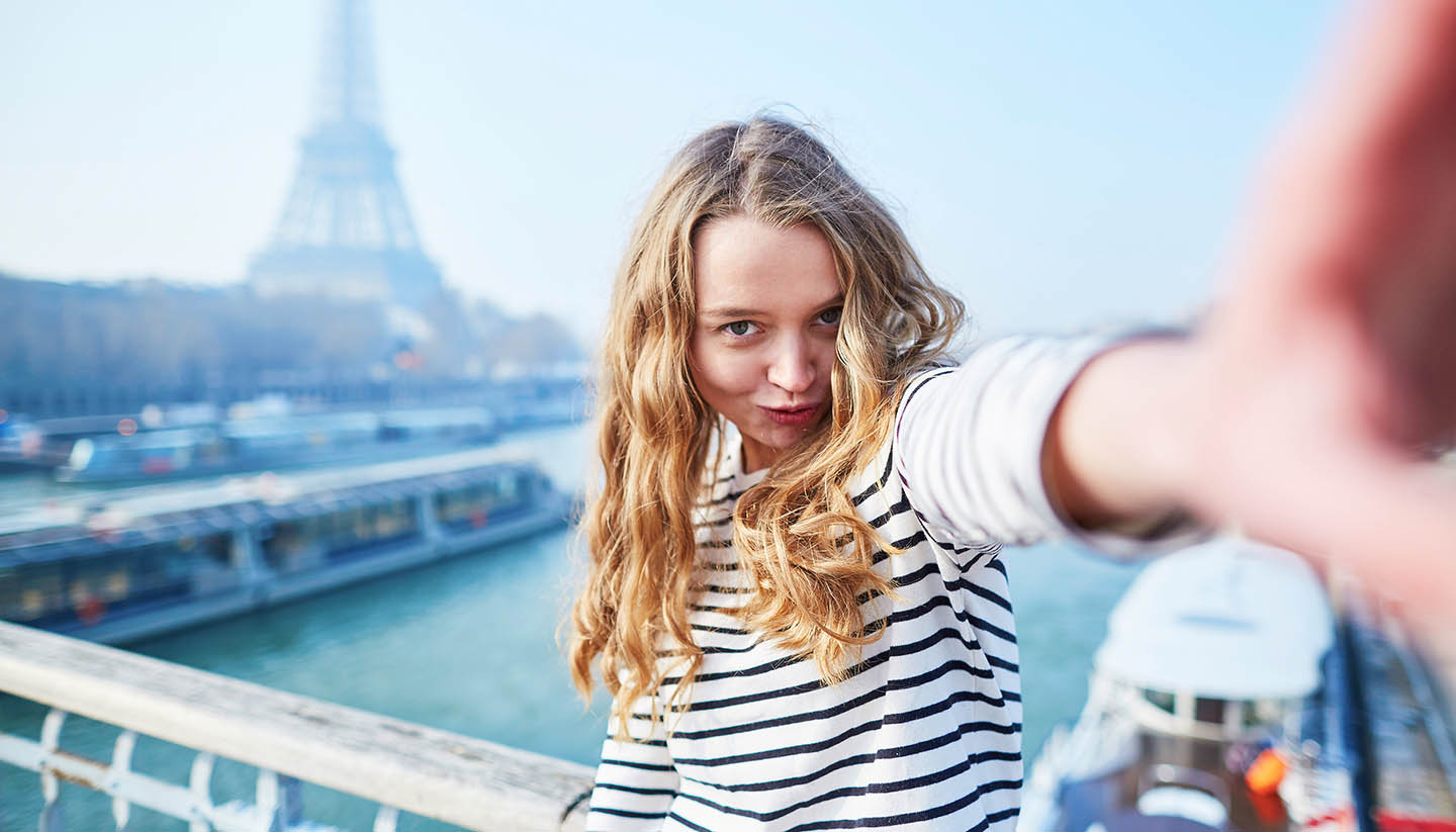 Paris - Young girl taking selfie near the Eiffel tower