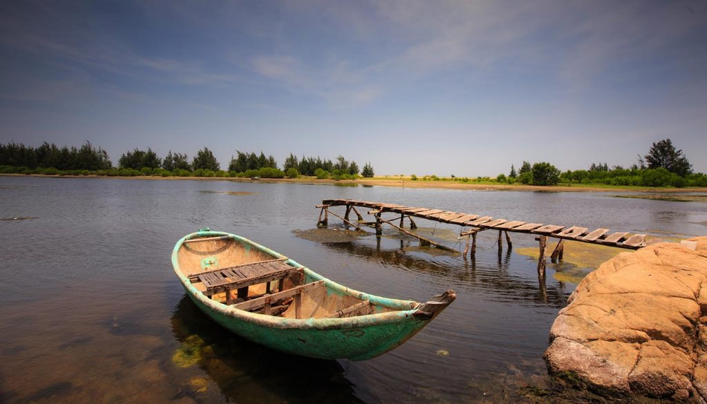 Guinea - Small pier with boat in a pond