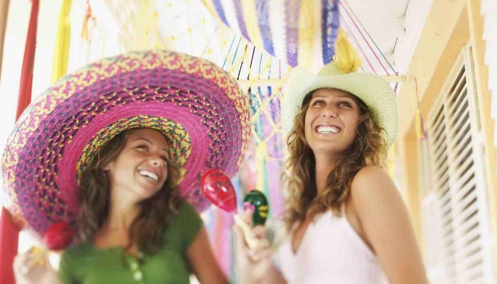 Mexiko - Smiling women with sombreros maracas