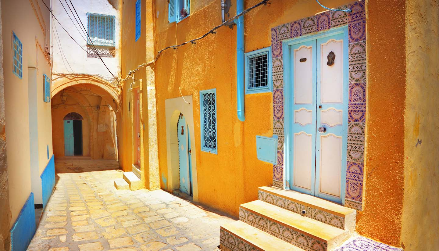 Tunesien - Arabian cobblestone street with orange colored building