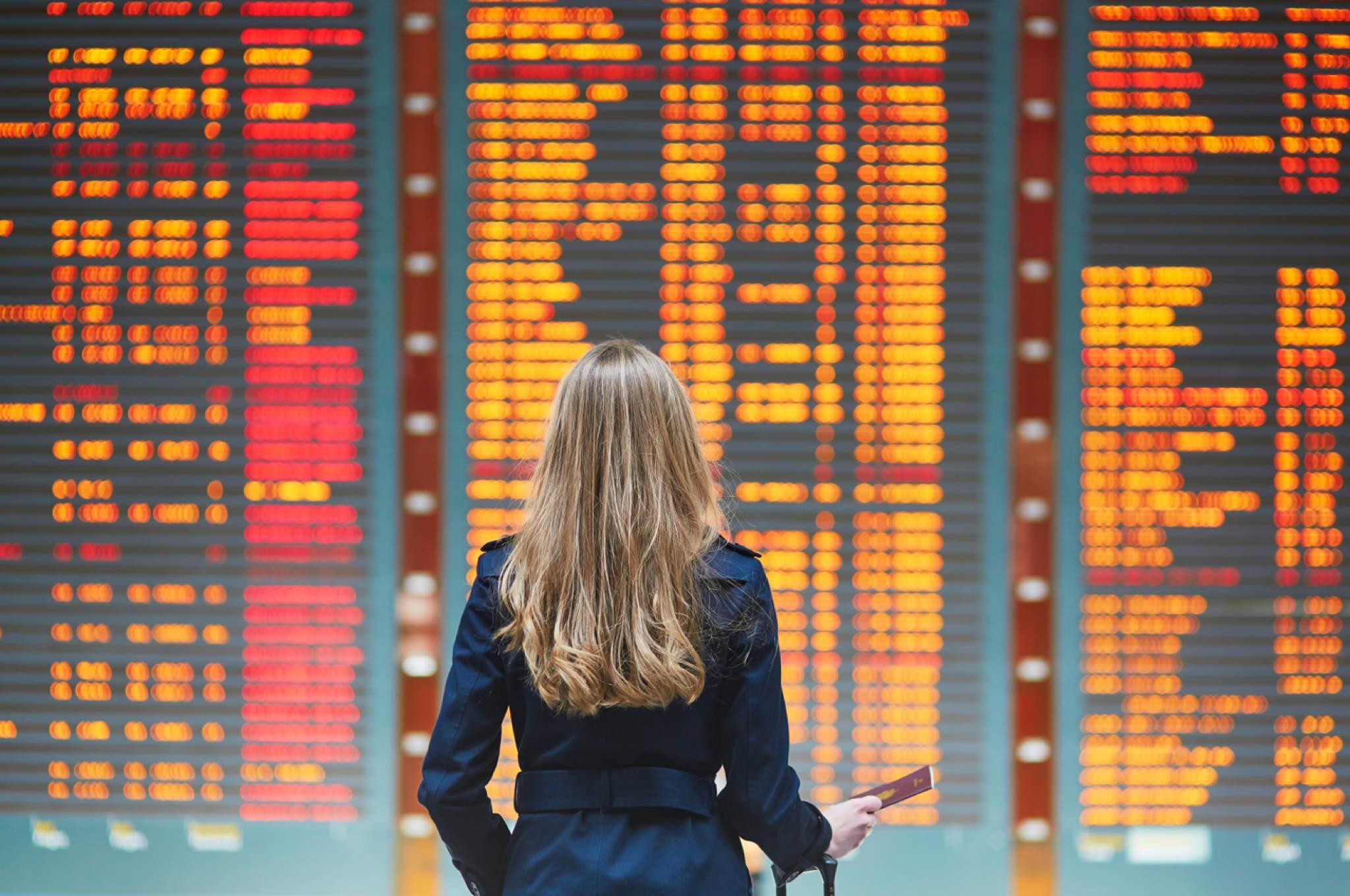 Über drei Stunden verspäteter Flug: Ihr Anrecht auf Entschädigung - Delayed flight - woman looks at departure board