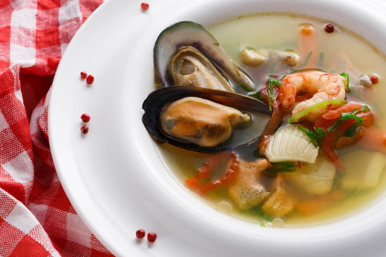 Meeresfrüchtesuppe mit Weißfisch, Garnelen und Miesmuscheln in einem mit Gewürzen garnierten Teller